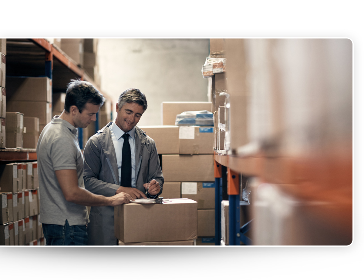 Smaller Corporate businessmen checking inventory in Newegg Logistics large warehouse
